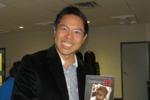 Thanh Campbell holds book